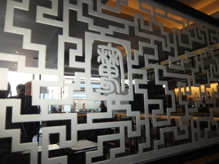 "A view of the dim sum bar through lattice work decorated with the ""Demon Chef's"" emblem"